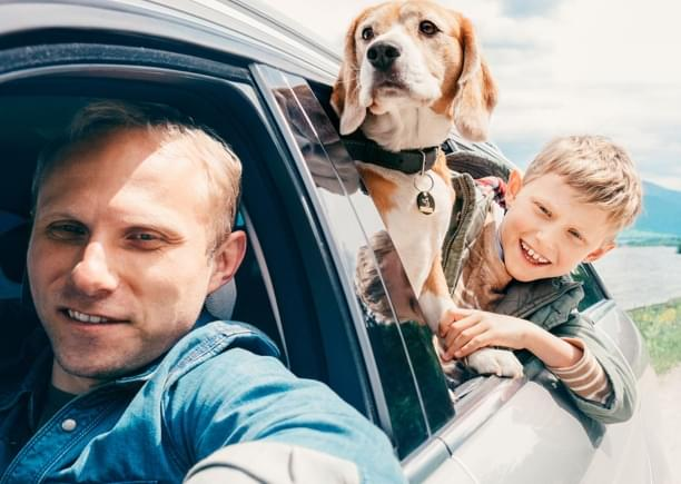 family with dog driving